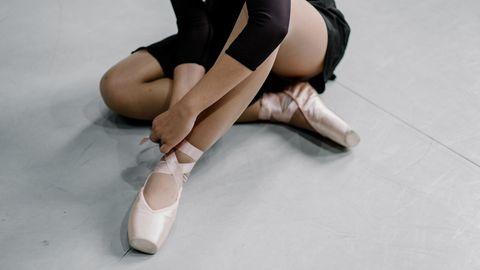 Eine junge Ballerina sitzt auf dem Boden und zient sich Ballettschuhe an