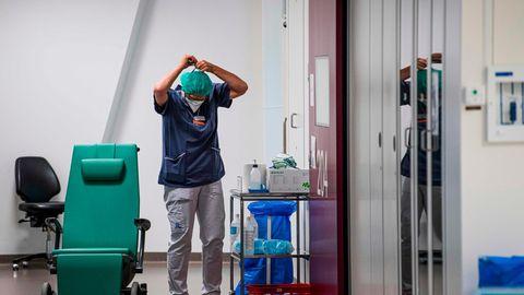 Eine Pflegekraft zieht sich einen Mund-Nase-Schutz in einem Stockholmer Krankenhaus an