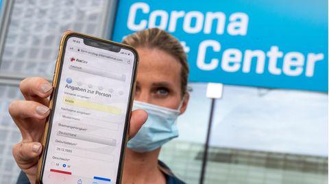 Eine Frau hält ihr Smartphone in die Kamera, mit dem sie sich zuvor am Flughafen für den Coronatest angemeldet hat.