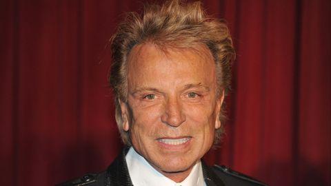 Ein älterer Mann mit blonder Wuschelmähne steht im Anzug vor einem weinroten Vorhang und lächelt