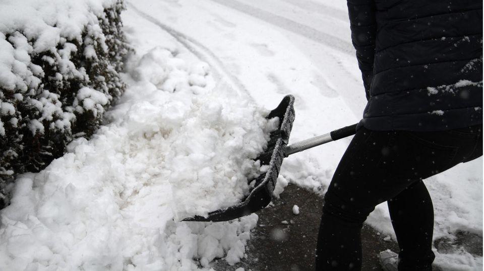 Morgenlage: Person beim Schneeschippen
