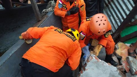Drei Männer in orangen Overalls und Helmen knien auf den Trümmern eines Gebäudes und schauen durch einen Spalt ins Dunkel