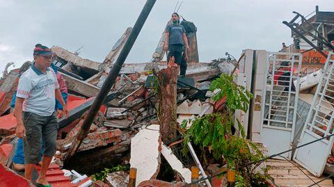Anwohner inspizieren beschädigte Häuser