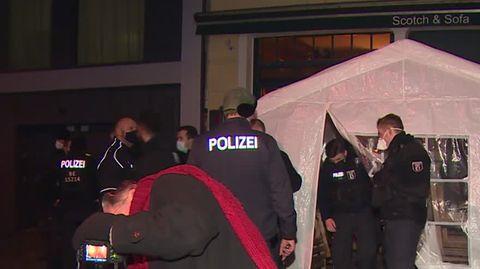 Vor einer Bar in Berlin steht ein weißes Partyzelt. Ein Polizist steht neben dem Zelteingang, ein zweiter kommt gebückt heraus