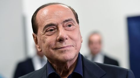 Ein Mann mit hoher Stirn und schwarzen Haaren legt den Kopf schräg und lächelt