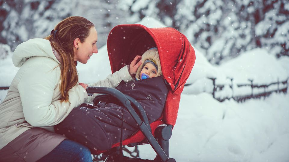Winterfußsack: Mutter streichelt ihr Kleinkind, das im Buggy in einem Winterfußsack liegt