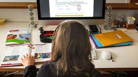 Ein Kind löst am Computer Schulaufgaben.