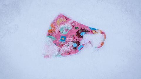 Ein verlorener, bunt gemusterter Mund-Nasen-Schutz für Kinder liegt im Schnee auf dem Gipfelplateau des Großen Feldbergs