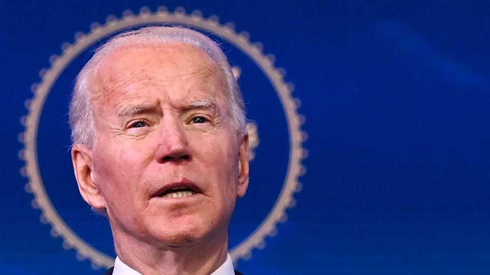 Vor einem blauen Hintergrund steht der künftige US-Präsident Joe Biden und gestikuliert bei einer Rede mit beiden Händen