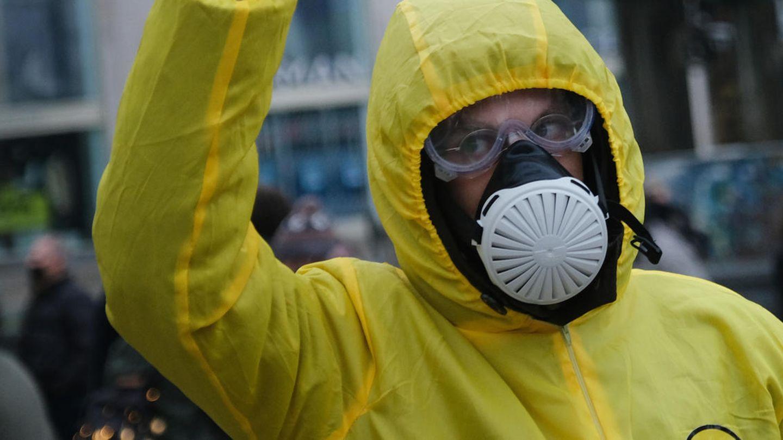 """Bei einer """"Querdenken""""-Demo in Berlin trägt ein Mann einen gelben Overall mit Kapuze sowie Schutzbrille und Atemmaske"""