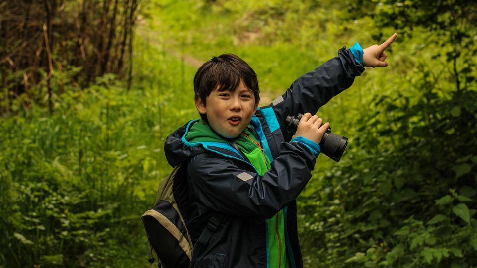 Eine Junge mit Fernglas weist den Weg