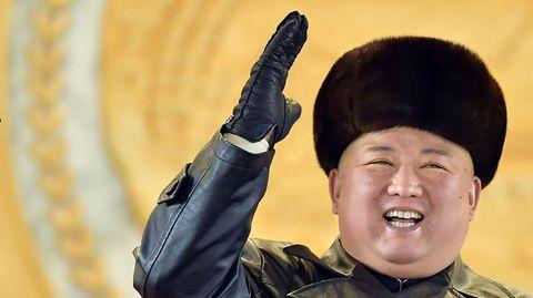 Mit schwarzer Pelzmütze und schwarzem Glattleder-Mantel steht ein übergewicchtiger Asiate vor einer goldgelben Wand und winkt