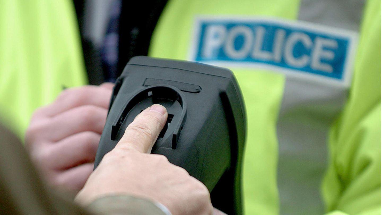 Ein Beamter der Verkehrspolizei demonstriert einen mobilen Fingerabdruckanalysator