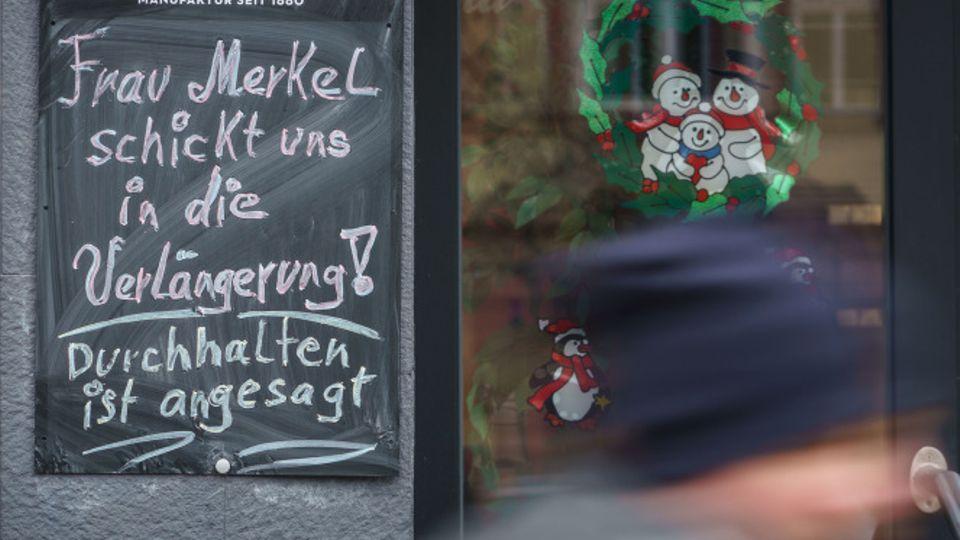"""""""Frau Merkel schickt uns in die Verlängerung! Durchhalten ist angesagt!"""" steht vor einem geschlossenen Geschäftin Friedberg."""