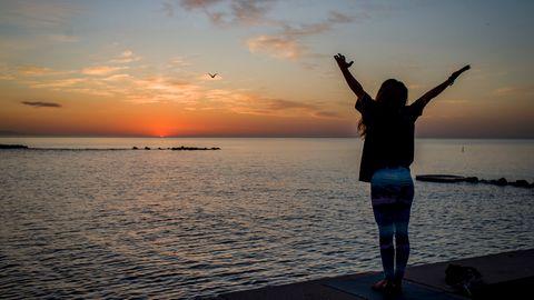 Eine Frau steht vor dem Meer und wirft die Arme hoch