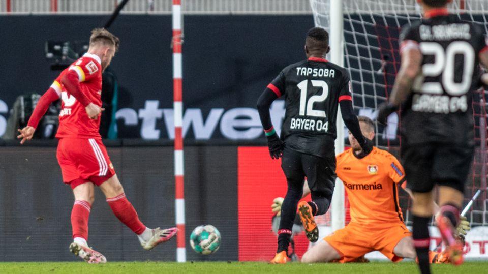 Berlins Cedric Teuchert (l) trifft zum 1:0 gegen Torwart Lukas Hradecky (r) von Bayer Leverkusen.