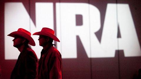 Zwei Männer mit Cowboyhüten stehen vor dem Logo der NRA