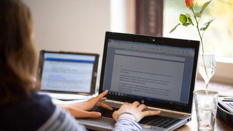 Ein Mädchen tippt auf einem Laptop