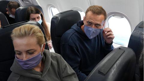 Kremlgegner Alexej Nawalny (r.) und seine Ehefrau Julia sitzen mit Mund-Nasen-Schutz in einem Flugzeug