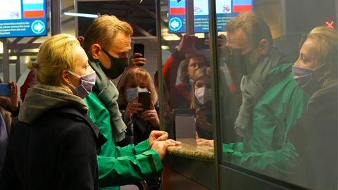 Alexej Nawalny (M.), der nach der Ankunft am Flughafen Scheremetjewo neben seiner Ehefrau Julia bei der Passkontrolle steht