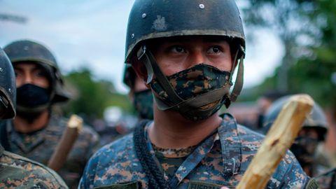 Ein Uniformierter in bläulichem Tarnfleck trägt Helm und hält einen hölzernen Schlagstock vor seiner Brust