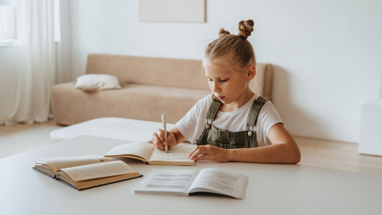 Ein kleines Mädchen sitzt zuhause über Schulbüchern