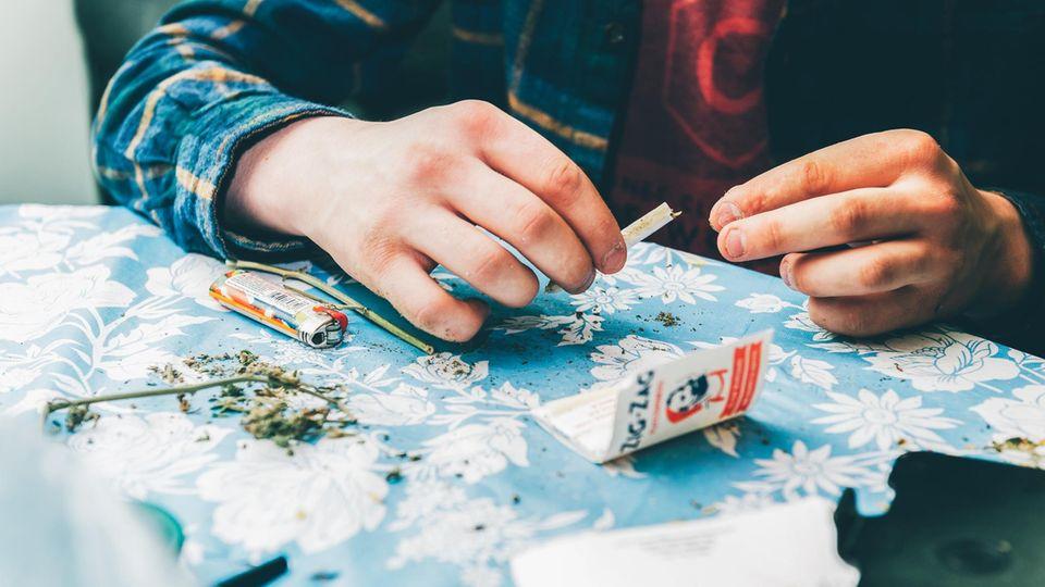 Ein junger Mann dreht sich einen Joint