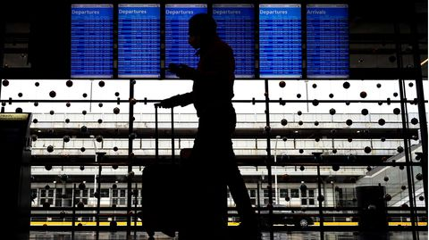 Ein Reisender trägt eine Gesichtsmaske, während er durch Terminal 3 am O'Hare International Airport in Chicago geht.