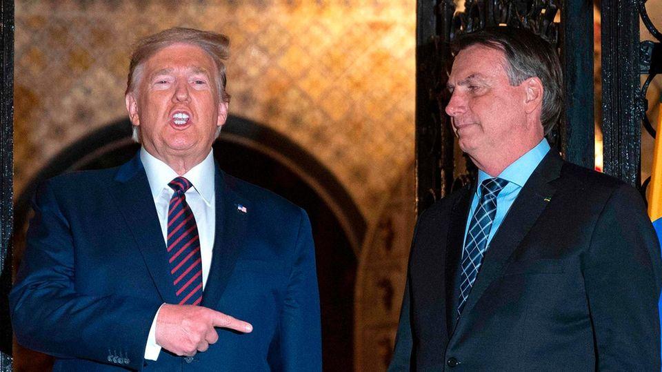 US-Präsident Donald Trump spricht und zeigt mit der rechten Hand auf den neben ihm stehenden Jair Bolsonaro