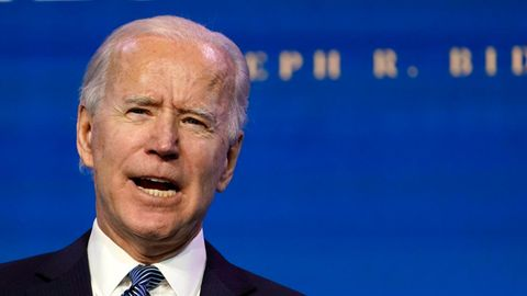 """Unter dem Schriftzug """"President"""" hält Joe Biden eine Rede und ballt die rechte Hand vor seiner Brust"""