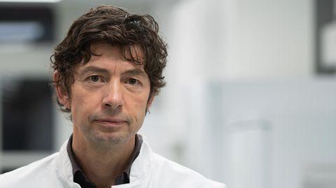 Ein Mann mit braunen Locken und im weißen Arzt-Kittel steht auf einem Klinik-Flur