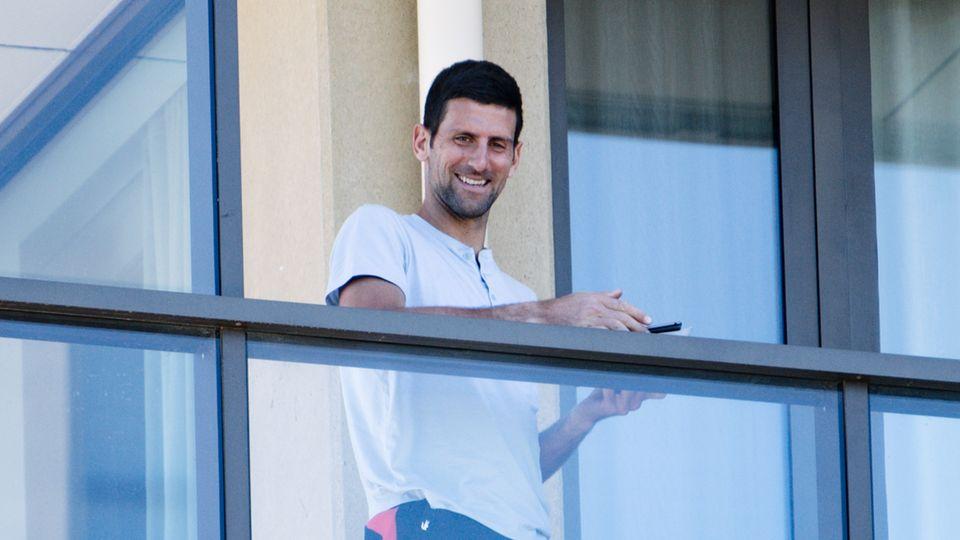 """Tennisspieler Novak Djokovic aus Serbien steht auf einem Balkon der Unterkunft """"The M Suites"""" in North Adelaide und schaut jungen Fans beim Tennisspielen zu."""
