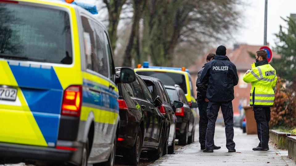 Polizisten stehen in einer Straße nahe des Parkplatzes, auf dem eine Frauenleiche in einem Auto gefunden wurde