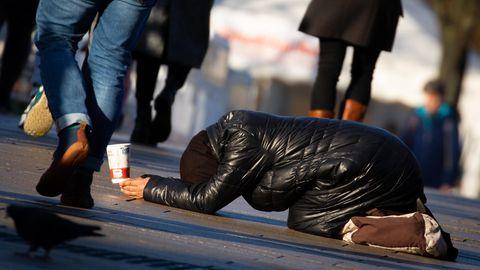 Tief gebeugt kniet eine Frau auf einem Fußweg zwischen vorbeigehenden Passanten und bittet um Geld