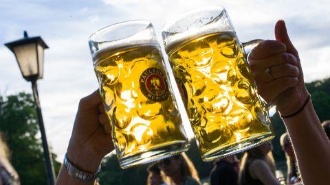 Zwei Personen prosten sich in einem Biergarten mit zwei Maßkrügen zu.