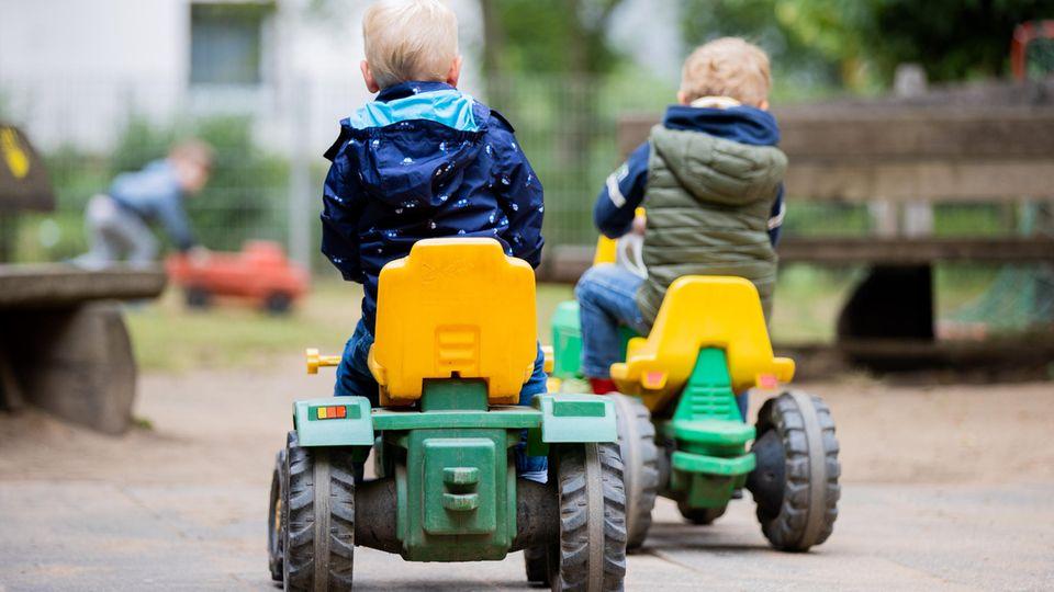 Zwei Kleinkinder spielen im Garten eines Kindergartens.