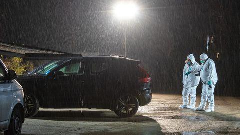 Mitarbeiter der Spurensicherung untersuchen auf einem Parkplatz den Fundort einer Frauenleiche