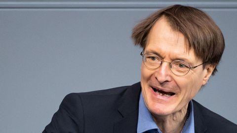 SPD-Gesundheitsexperte Karl Lauterbach steht in blauem Anzug am Rednerpult im Bundestag und gestikuliert mit der rechten Hand