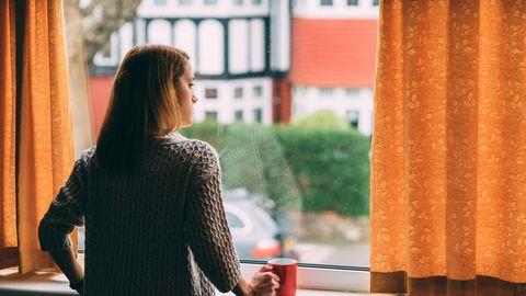 Eine junge Frau guckt aus dem Fenster