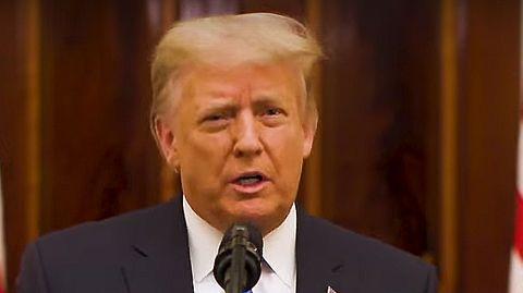 Donald Trump steht an einem Rednerpult mit dem Siegel des US-Präsidenten und spricht. Im Hintergrund US-Flaggen