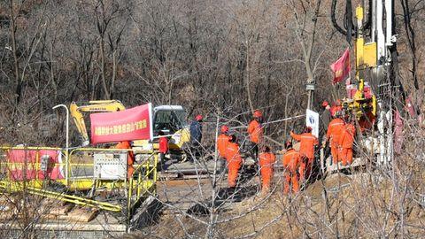 Männer in orangen Overalls und roten Sicherheitshelmen stehen um ein großes gelbes Bohrgestänge herum