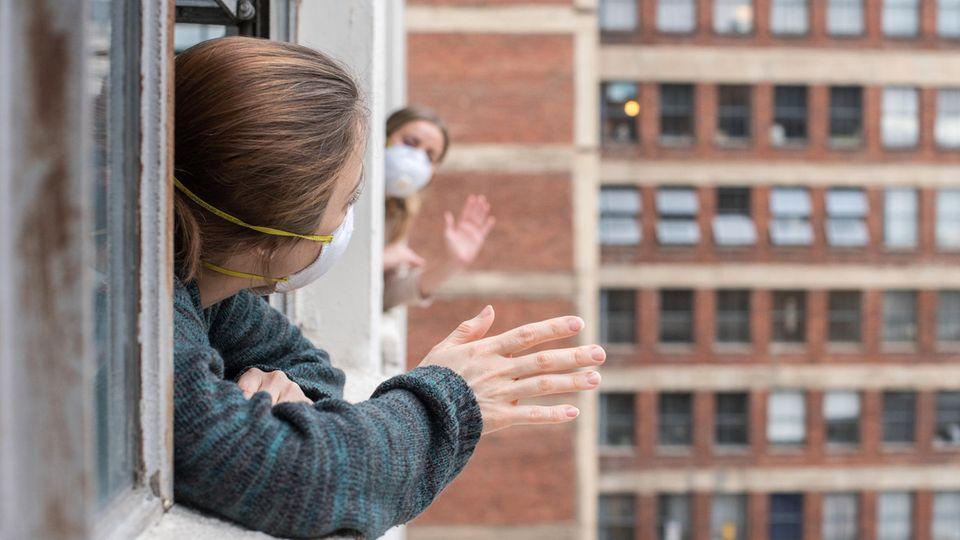 Nachbarn winken sich aus dem Fenster zu