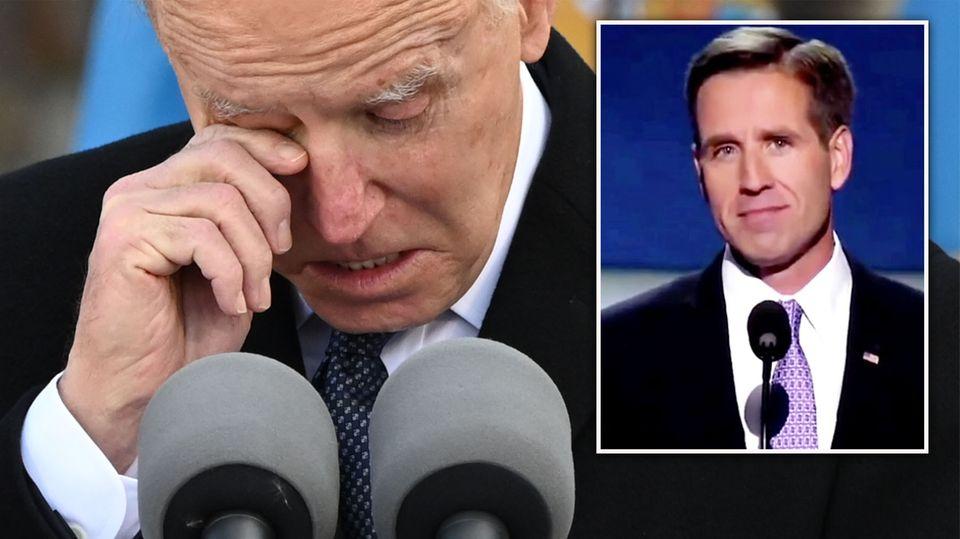 In schwarzem Mantel und Krawatte steht Joe Biden vor zwei Mikrofonen und wischt sich mit der rechten Hand eine Träne ab