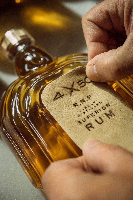 Das Leder-Etikett der Flasche wird händisch befestigt