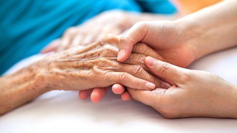 Altenpflege: Eine junge Frau hält die Hand einer älteren Frau