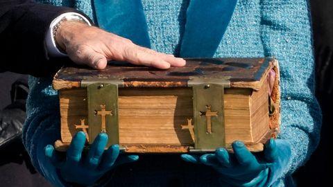 Joe Biden hält eine Hand auf einer historischen Bibel