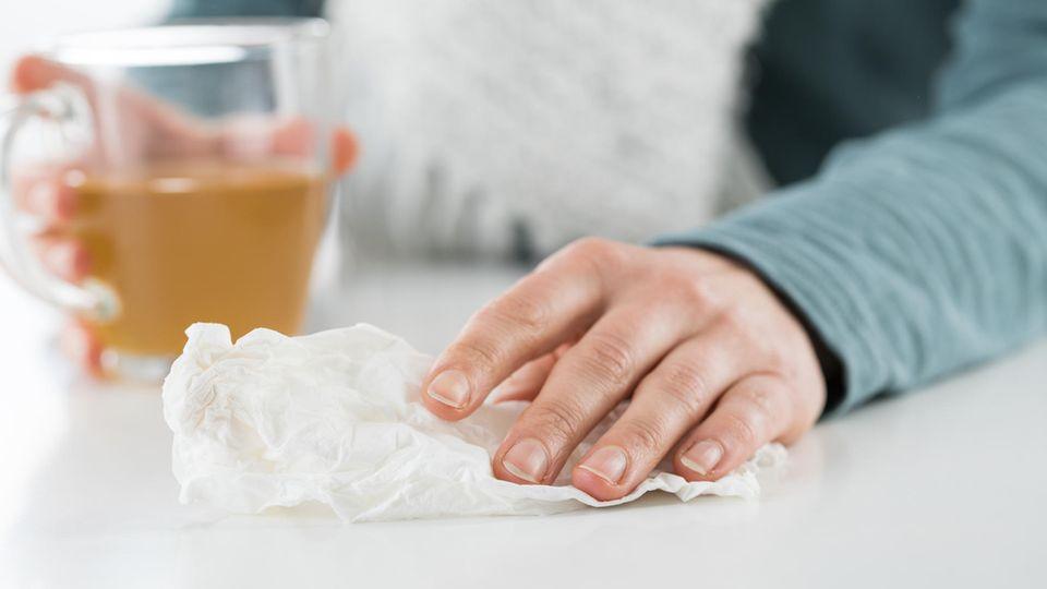 Eine Frau sitzt in einem Studio in Hamburg und trinkt Tee