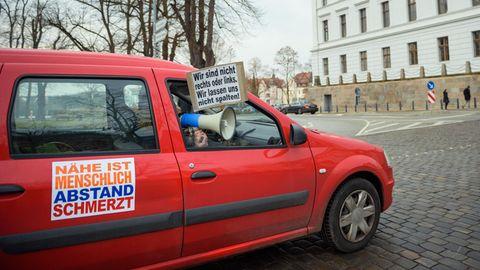 Ein Fahrzeug mit Plakaten, auf denen Slogans gegen den Lockdown stehen