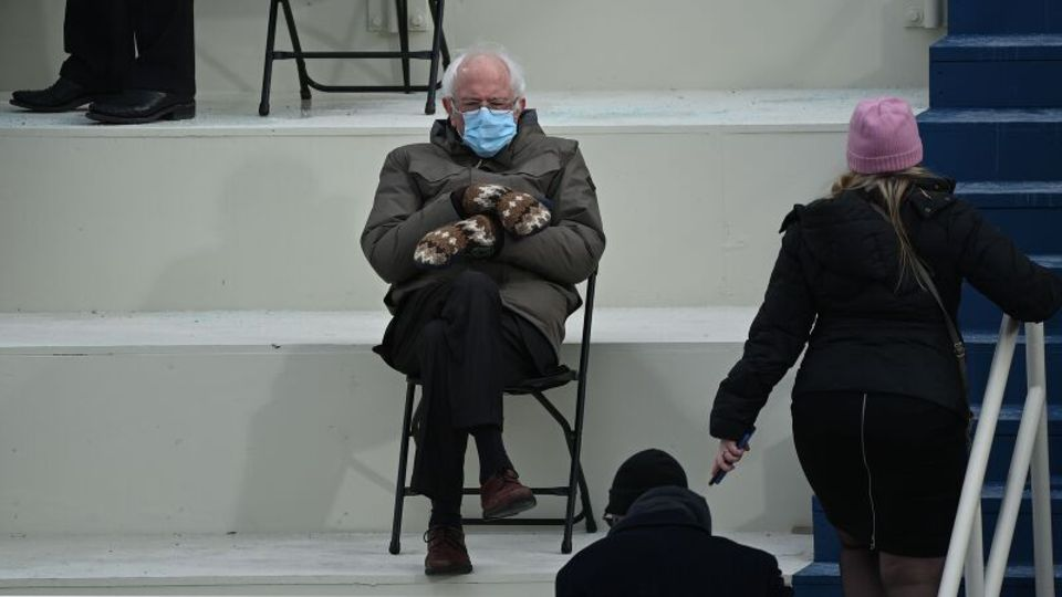 Bernie Sanders trägt Fäustlinge und sitzt auf einem Klappstuhl