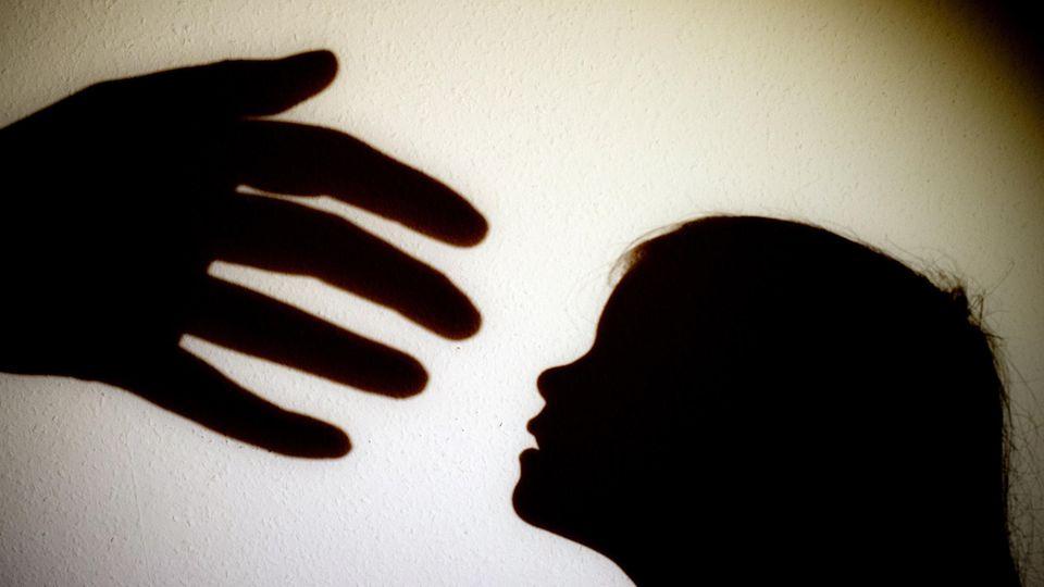 Schatten einer Hand einer erwachsenen Person und der Kopf eines Kindes an einer Wand eines Zimmers.